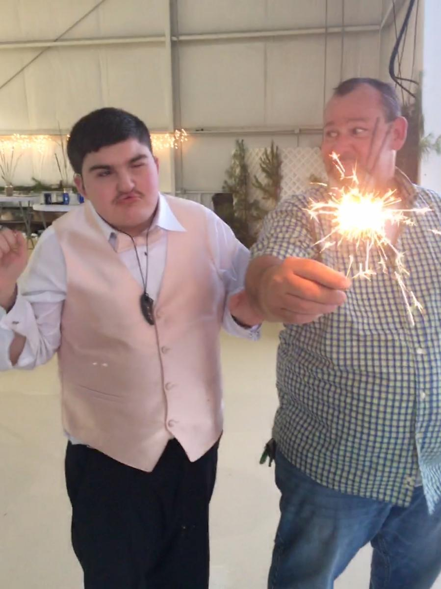 Andrew watching a sparkler at wedding.