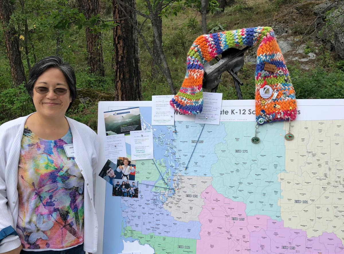 A woman standing next to the map of WA with scarf.